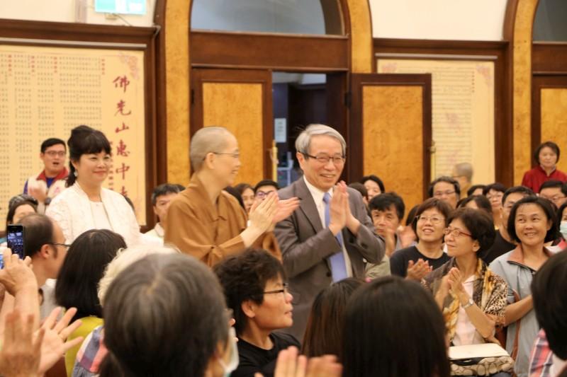 「台灣國寶」鄭隆賓院長在覺居法師引導走進大講堂,受到聽眾熱情的歡迎。